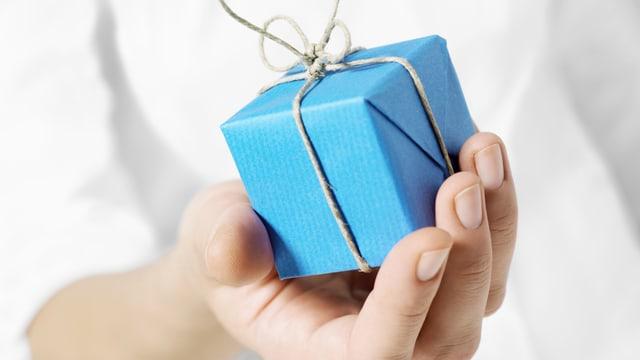 Eine Hand hält ein Geschenk.