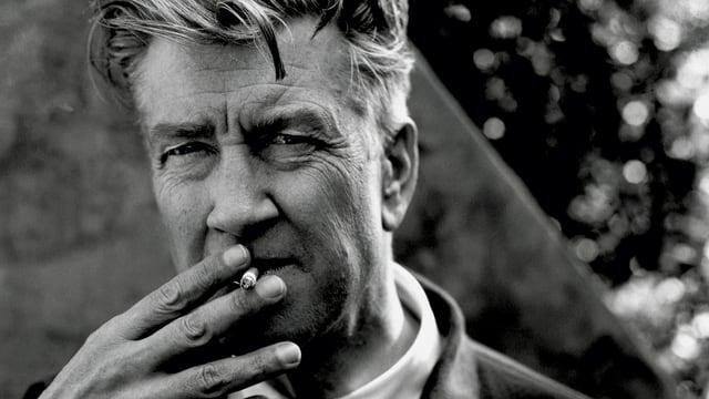 Porträt von David Lynch mit einer Zigarette im Mund.