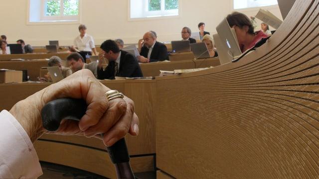 Parlamentsbetrieb, im Vordergrund die Hand einer Greisin an einem Stock