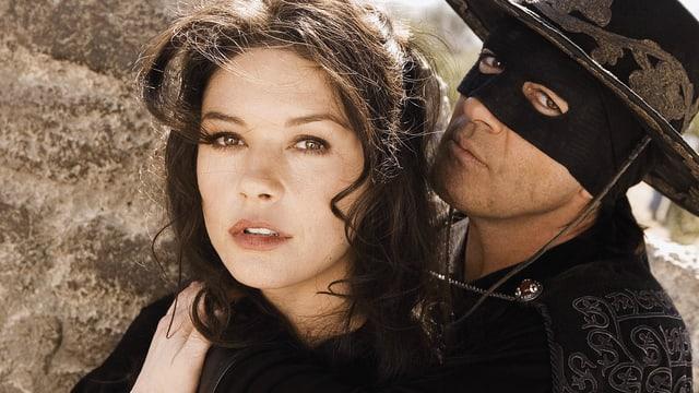 Ein Mann mit einer Zorro-Maske umarmt eine Frau.