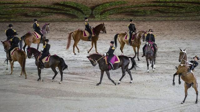 Reiter reiten mit ihren Pferden an der Eröffnungsfeier in Caen im Kreis.