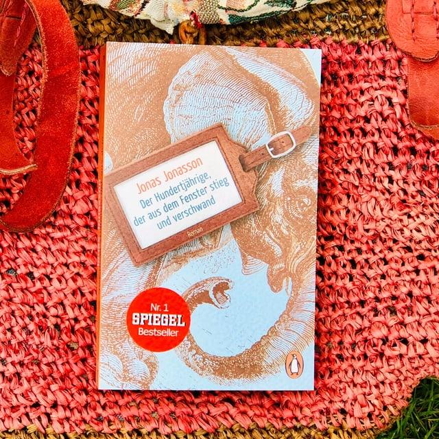 Der Schelmenroman «Der Hundertjährige, der aus dem Fenster stieg und verwand» von Jonas Jonasson liegt auf einer Beuteltasche