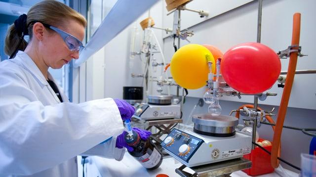 Die Mitarbeiterin trägt Schutzbrille und weissen Kittel. Sie holt eine Substanz aus einer Flasche, rechts daneben eine Waage.