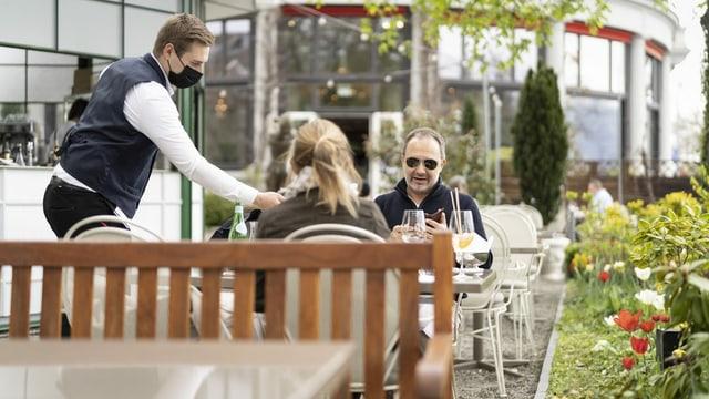 Ein Kellner bedient Restaurantgäste auf der Terrasse.
