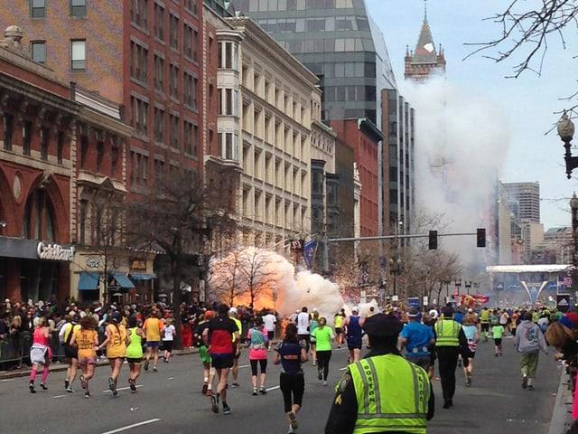 Menschen rennnen - im Hintergrund sieht man Feuer.