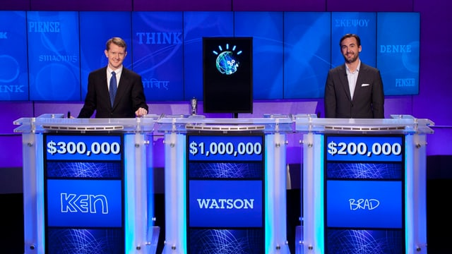 Zwei Männer und ein Computer stehen hinter den Kandidatenpulten der US-Quizshow Jeopardy!