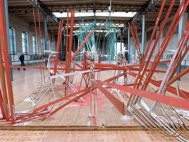 Rote Kunst-Installationen in einer Halle.
