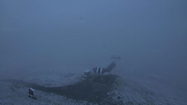 Verschneiter Berghang mit Skiliftbergstation.