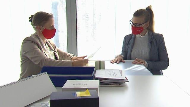 Zwei Frauen in Anzügen und mit roten Masken sitzen an einem Tisch. Auf dem Tisch liegen Papier und Ordner.