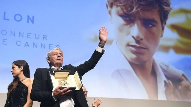 Alain Delon steht auf einer Bühne und hält die Goldene Palme in der Hand. Hinter ihm ist ein grosses Porträt von ihm in jungen Jahren.