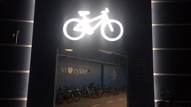 Velokeller bei Nacht. Darüber leuchtet ein Neon-Velo.