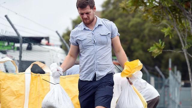 Ein Bewohner von Morningside, ein Vorort von Brisbane, trägt Sandsäcke.