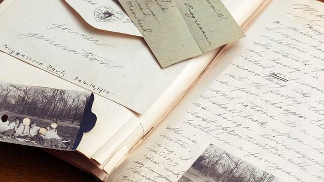 Ein offenes Notizbuch mit handgeschriebenem Text, daneben sind schwarz-weiss Fotos eingeklebt.