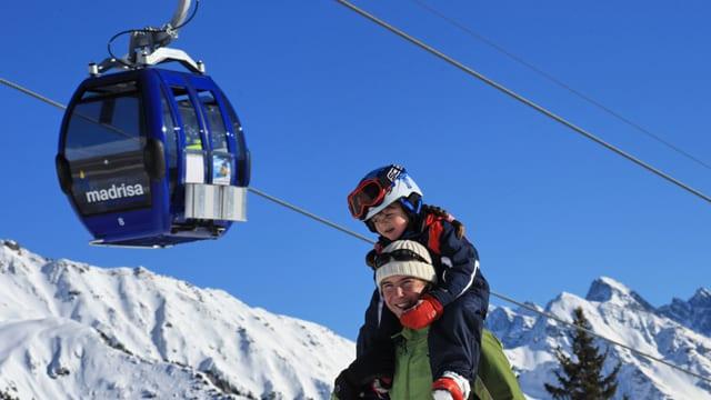 Mamma ed uffants sin skis avant ina cabina da la Madrisa.