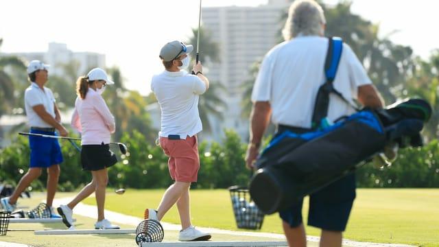Golfer spielen auf der Driving Range Bälle und tragen Schutzmasken.