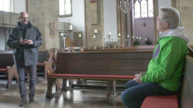 Mindens Pfarrer Frieder Küppers sitzt in seiner Kirche (weltlich bekleidet mit grüner Outdoor-Jacke) und tippt eine «gute Botschaft in sein Handy.