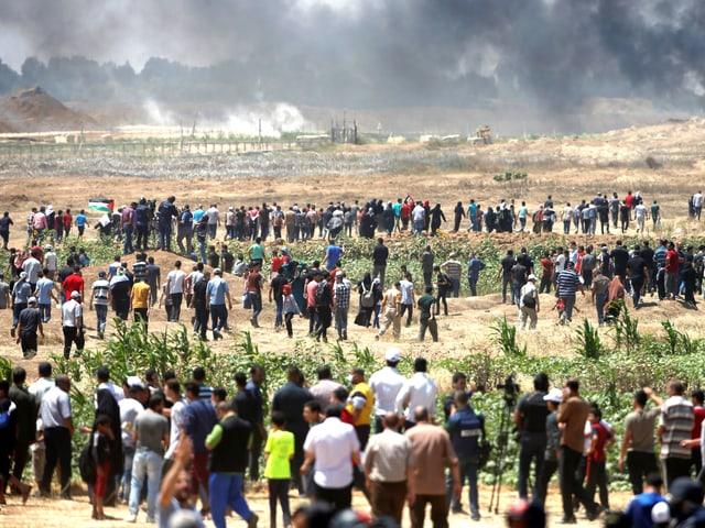Grosse Menschenmenge im Gazastreifen. Der Horizont ist mit schwarzen Wolken verhangen.