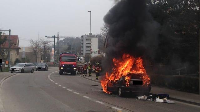 Brennendes Auto, dahinter Ferwehrfahrzeug.