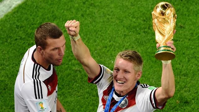 Lukas Podolski und Bastian Schweinsteiger mit dem WM-Pokal.