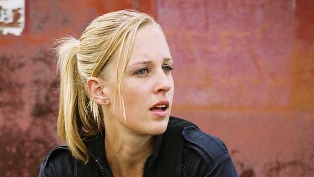 Eine blonde Frau in Uniform kniet am Boden und hat eine Waffe in der Hand.