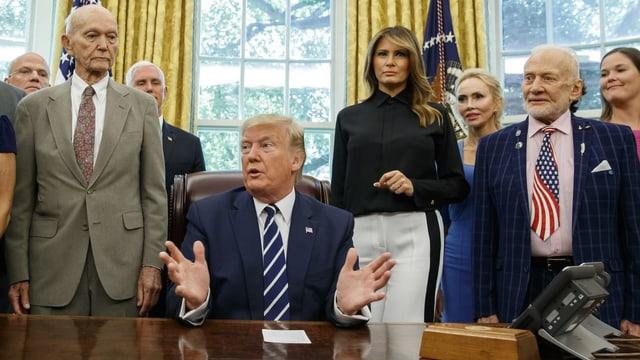 Trump an einem Tisch sitzend. Dahinter stehend (v.l.n.r.): Michael Collins, Mike Pence, Melania Trump und Buzz Aldrin.