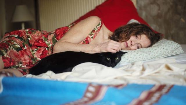 Eine Frau liegt auf einem Bett. Eine schwarze Katze liegt neben ihr.