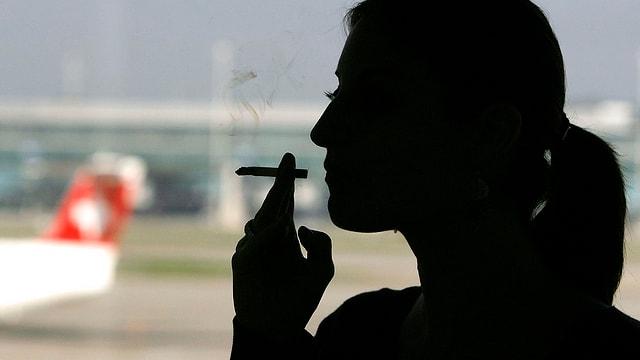 Symbolbild: Eine Frau raucht auf dem Flughafen im Gegenlicht.