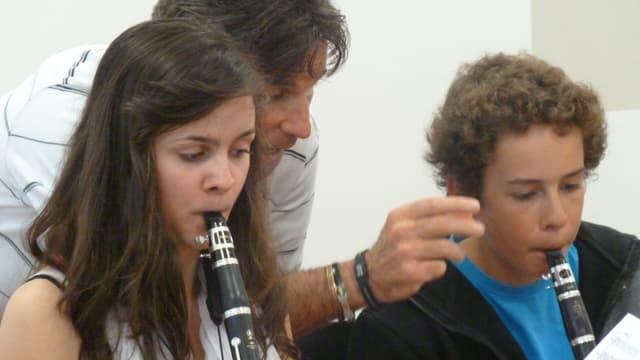 Dus giuvens che sunan la clarinetta, magister dirigia.