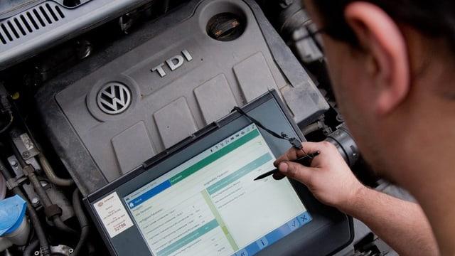 Ein Mechaniker schaut sich mit einem Lesegerät den Motor eines VW an.