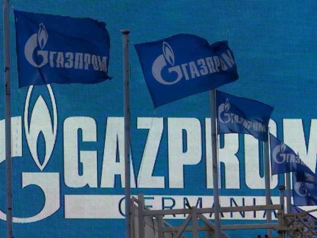 Flaggen vor einem Logo von Gazprom.