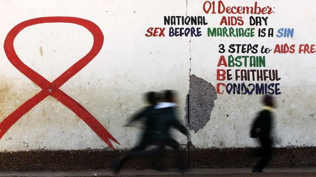 Eine Mauer, auf die eine Aidschleife und Präventions-Tipps gemalt wurden.