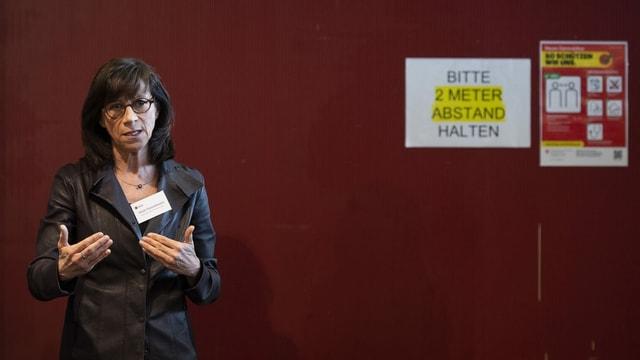 Eine Frau steht vor einer roten Wand; auf einem A4-Blatt wird darum gebeten, zwei Meter Abstand zu halten.