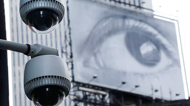 Zwei Überwachungskameras, im Hintergrund ein grosses Plakat, auf dem ein grosses Auge abgebildet ist.