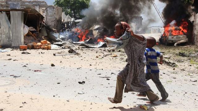Zwei Kinder gehen über einen Platz, im Hintergrund brennen Autos und Häuser.