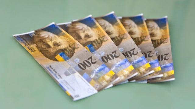Fünf 200 Franken-Noten aufgefächert auf einem Tisch.