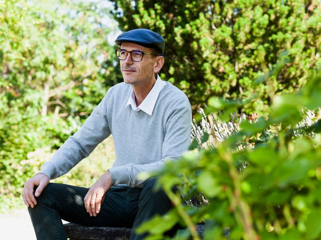 Simon Gebs sitzt im Grünen.
