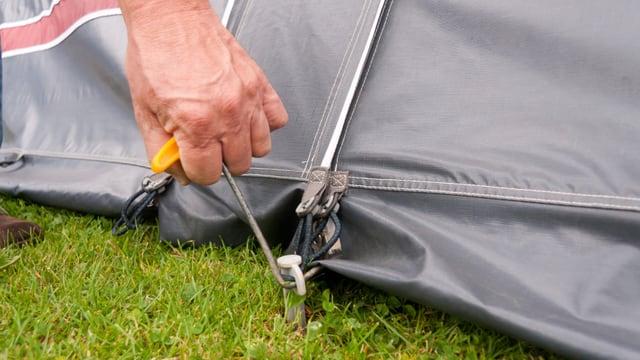 Ein Mann entfernt einen Zelthering aus dem Boden.
