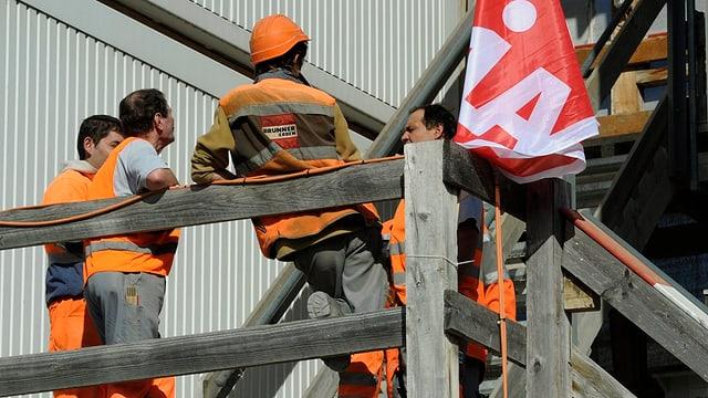 Purtret da lavurers che stattan enturn sin in plazzal. Ina bandiera dal sindicat UNIA penda dasperas.