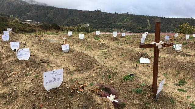 ein Feld mit einem Holzkreuz und einigen Namensschilder
