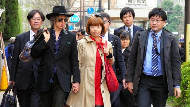 Eine japanische Frau, umgeben von Männern in Anzug.