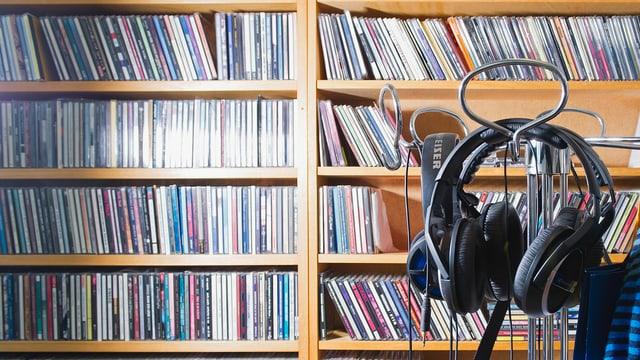 Ein Regal voller CDs davor ein Ständer mit Kopfhörern