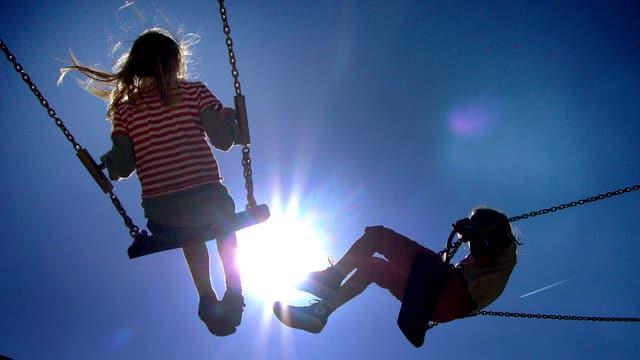 Aufnahme von zwei Kindern auf einer Schaukel.