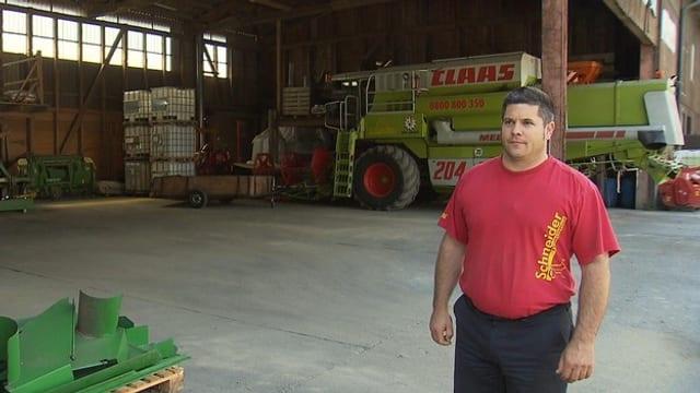 Ein Bauer steht vor seinen Maschinen