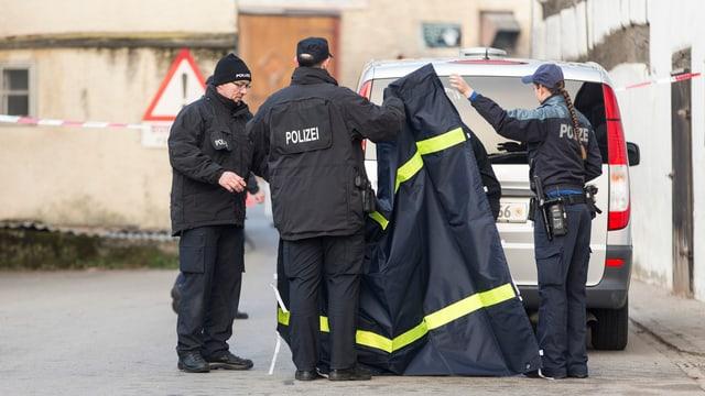Polizisten vor dem Haus, in dem die Tat geschah