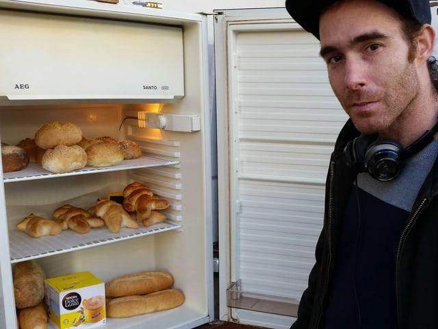 Tobias Vega vom Verein «Olten im Wandel» vor einem der beiden Kühlschränke der Restessbar. Im Kühlschrank befinden sich Brote und andere Backwaren.