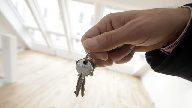 Hand hält Schlüssel vor nigelnagelneuer leerer Wohnung