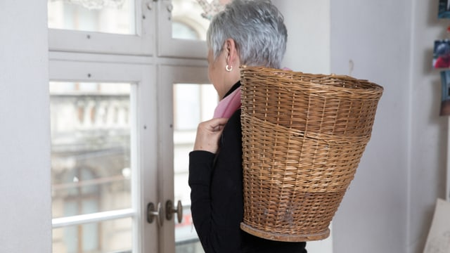 Eine Frau schaut aus dem Fenster. Auf ihrem Rücken trägt sie einen Korb.