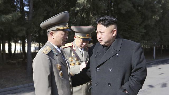 Kim Jong Un steht neben zwei Offizieren.