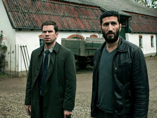 Zwei Männer vor einem Bauernhof.