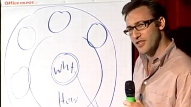 Ein Mann mit Brille und Mikrofon vor einer Skizze an einer Tafel.